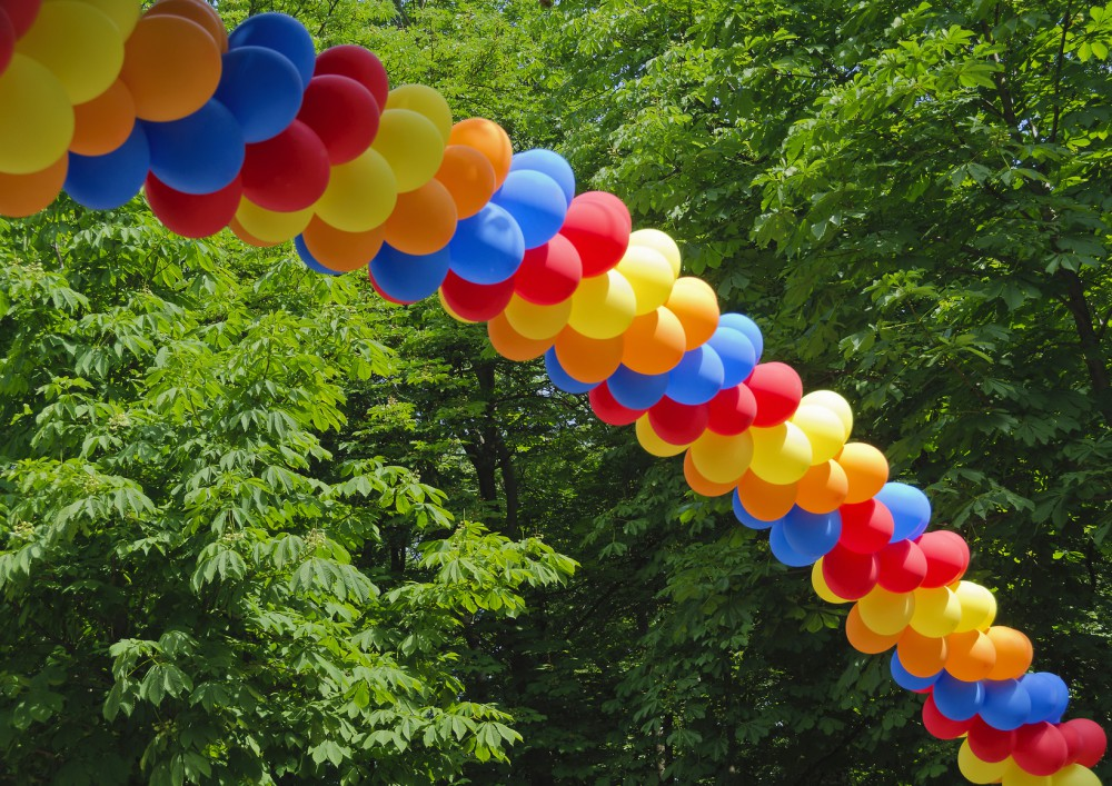 Bogen aus bunten Luftballons schwebt vor Waldbäumen; arch made from colorful balloons hovering in front of forest trees