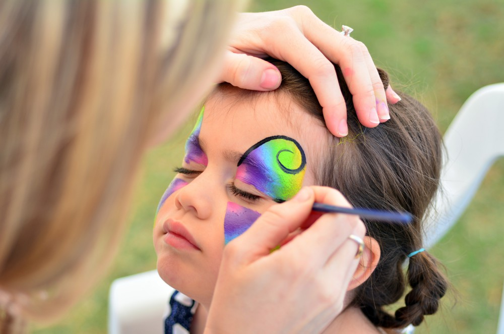 little girl getting her face painted like a butterfly.